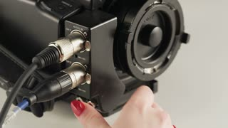 Woman Re-plugging Two Cables to a Video Camera