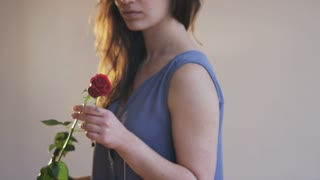 Woman Smelling a Red Rose and Throwing it Away