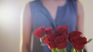 Woman Takes a Bouquet of Red Roses