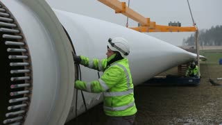 Worker Pressing Tape to The Rotor Blade