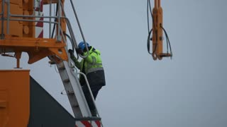 Worker Walking Down the Ladder and Leaving the Crane