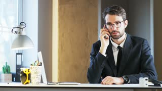 Young Businessman Feeling Distracted While Talking on the Phone