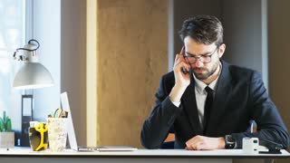 Young Businessman Having a Headache and Ending a Phone Call