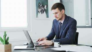 Young businessman using both a laptop computer and a mobile phone.