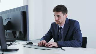 Young businessman yawns while looking at a stationary computer.