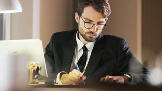 Young Businessman Writing and Thinking Deeply