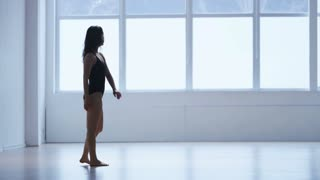 Young Woman Training Modern Dance in a Gym