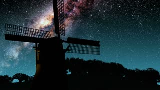 old windmill and Milky Way stars at night. Elements of this image furnished by NASA
