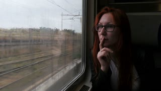 4K Attractive woman in thought looking out of a train window