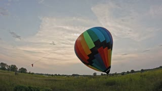 A balloon crew inflates the envelope of their hot air balloon, wide angle