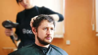 A bearded an in barbershop - hairdresser moves around and makes men haircut, time lapse
