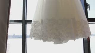 A bride's wedding dress on the window