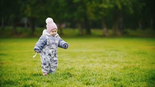 A child - little girl walking in autumn park: a baby running at the meadow, slow motion