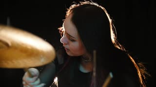 A female percussion drummer performing with drums, slow motion