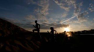 A group of athletes - two girls and a guy are fleeing the mountain, near river at dusk, slow-motion, silhouette