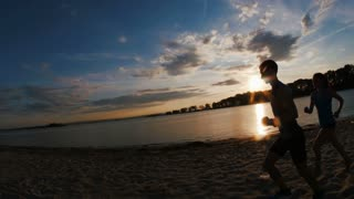 A group of athletes - two girls and a guy runs on beach, near river at sunset, silhouette, slow-motion, run past