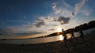 A group of athletes - two girls and a guy runs on beach, near river at sunset, silhouette, slow-motion, wide angle