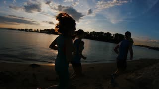 A group of athletes - two girls and a guy runs on beach, near river at sunset, silhouette, slow-motion