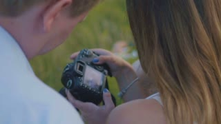 Adult couple posing for female photographer during fashion photo shoot outdoor, close up