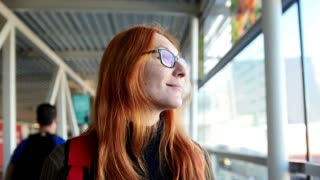 Airport - happy woman with red hair and glasses taking the escalator and looking to window