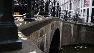 Amsterdam canal, early morning, cloudy day, Autumn, details - bridge, bicycles, tourists
