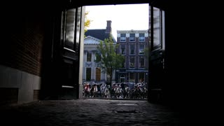 AMSTERDAM, NETHERLANDS - view of street with tourists, bicycles and canal, silhouette