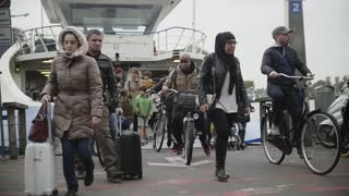 AMSTERDAM, THE NETHERLANDS. 18 oct 2016: Ferry to buiksloterweg - pedestrians, bikes, scooters - passengers leave the vessel
