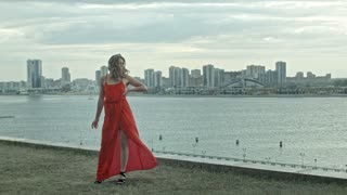 Attractive girl in a red dress stands over the citi in the wind with fluttering dress