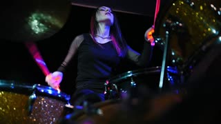 Attractive girl playing electronic drums on stage. Concert - red Neon light, slow motion