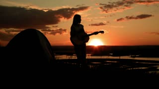 Attractive romantic girl playing the acoustic guitar, at sunset near camping on high hill, silhouette