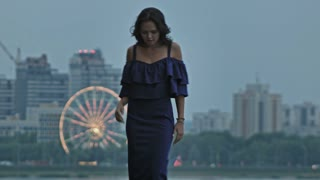Attractive young woman fashion model in party dress posing outdoor in front of Ferris wheel, wide shot