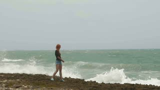 Attractive young woman with long red hair standing on the coast and looking to the storm sea, throws pebbles, slow-motion, wide angle