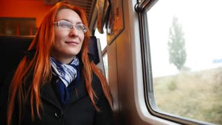 Attractive young woman with red hair and glasses looking out of a train window