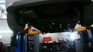 Automobile car diagnostic - mechanic working under a lifted car, slider