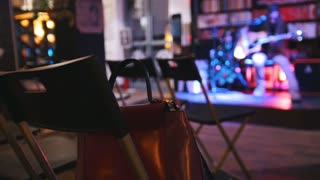 Bag is on the chair - empty room in front of the guitarist at concert - acoustic guitar, microphone, club