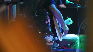 Bearded guitarist at concert - acoustic guitar, microphone, club