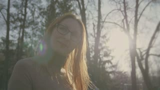 beautiful girl with red hair wearing glasses goes in the park slo-mo