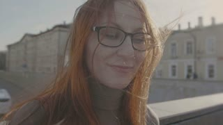 beautiful girl with red hair wearing glasses in street near highway looks in camera slo-mo
