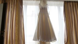 Beautiful wedding dress on window in bride's room