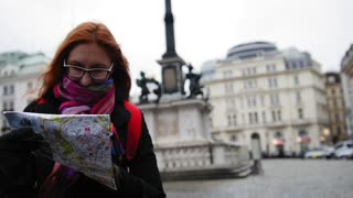 Beautiful young attractive woman tourist in glasses standing at plaza and uses map in center city Vienna