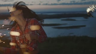 Beautiful young woman dancing on a high hill with sparkler at sunset in slow motion