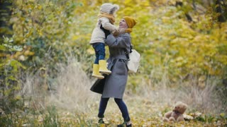 Beautiful young womans - mother with her daughter walking and laughing in autumn forest, slow motion