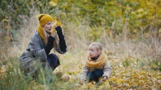 Blonde little daughter with her mommy walks in autumn park - have funny and collect leaves