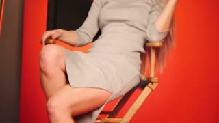 Blonde model girl in photo studio sitting on chair - fashion backstage