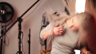 Blondy girl in photo studio playing with hair - fashion backstage