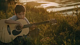 Boy in summer field training to play the guitar at summer sunset, on high hill