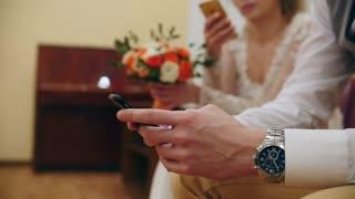 Bride and groom on wedding use Smartphones after wedding registration