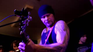 Brutal rock artist play guitar and sing microphone in night club