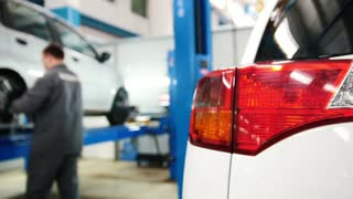 Car details - auto headlight close up in diagnostic service - mechanic working near lifted car