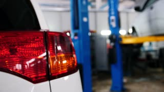 Car details - red auto headlight close up in diagnostic service - mechanic working near lifted car